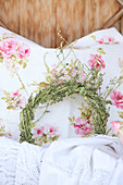 A scented herbal wreath on a pillow with a rose motif