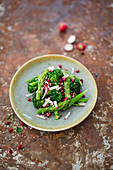 Salad with broccoli stems, radishes, pomegranate and green asparagus