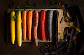 Four different carrots (yellow, orange, red and purple) partially peeled on a wooden board with a peeler and a napkin