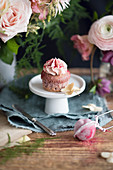 Strawberry milksake cucpcake with pink frosting on a mini cake stand surrounded by flowers