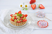 Strawberry tart with almond biscuits and pistachio cream, decorated with fresh strawberries and white chocolate (vegan)