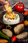 Woman hand dipping slice of bread inside melted Camembert cheese, seasoned with herbs and peppers