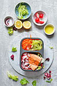 A healthy lunchbox with fish and salad