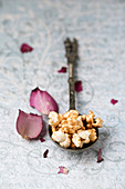 Gilded popcorn on a vintage spoon next to rose petals