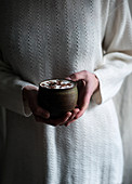 A woman holding a cup of vegan hot chocolate with soy cream