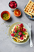 Banana waffles with fresh berries, blood oranges and pistachios