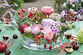 Rosen, Hagebutten, Stauden, Salbei und Kerzen als Tischgesteck