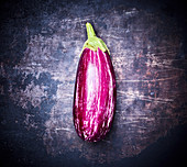 An eggplant on a dark metal background (top view)