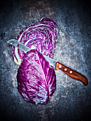 A halved red cabbage with a knife on a dark metal background