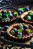 Mini tarst with strawberry jam and blueberiies. Decorated with mint leaves