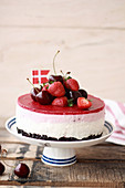 Berry mousse cake on a cake stand, topped with strawberries and cherries