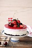 Beeren-Mousse-Torte auf Tortenständer mit Erdbeeren und Kirschen