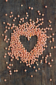 A heart made of red lentils on a wooden background
