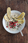 Porridge with caramelised banana halves, pomegranate seeds, chia seeds and pumpkin seeds