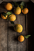 Scattered oranges on wooden surface