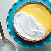 Making a lemon meringue tart: spread egg whites over the lemon cream