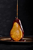 Chocolate pouring on a ripe pear