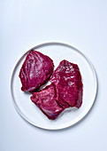 Three raw ostrich steaks on a plate against a white background (top view)