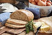 Frisch gebackenes Brot, teilweise in Scheiben, Butter und Rosmarin