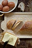 Frisch gebackenes Baguette, Butter und Eier