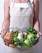 A woman holding a wire basket with fresh vegetables, milk and bread rolls