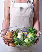 Frau hält Drahtkorb mit frischem Gemüse, Milch und Brötchen