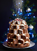 A Pandoro cake filled with cream and dusted with icing sugar, topped with Cranberries and sitting in from of a Christmas tree