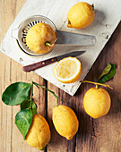 Lemons and lemon leaves on a rustic wooden surface