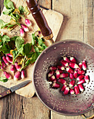 Washed and prepared radishes in a metal colander