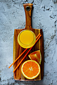 Fresh orange juice in a glass on a wooden board