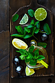 Green tea with lime, lemon and mint in a glass jug on a wooden board