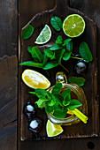 Geeister Grüntee mit Limette, Zitrone und Minze in Glaskrug auf Holzbrett