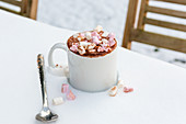 A cup of hot chocolate with marshmallows on a table in the snow