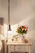 Strauß Rosen in einer Kaffeekanne auf dem alten Nachttisch