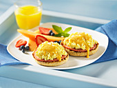 Eggs Benedict mit Schinken und Obst