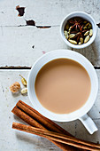 Grunge wooden table with traditional Indian masala tea in white ceramic cup and spices (cinnamon, anise, cardamom, sugar)