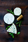 Top view of rustic kitchen table with different kinds of cheese, olives, basil and rosemary on dark wooden background