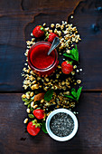 Freshly made strawberry puree, chia seeds, granola, fresh berries and mint for breakfast or smoothie. Healthy ingredients on dark wooden background