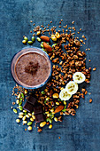Delicious banana chocolate smoothie with homemade granola, nuts and seeds on dark vintage backdrop