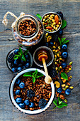 Top view of chocolate granola in open jar and honey served with berries, nuts and fresh mint for tasty breakfast on rustin wooden table