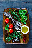 Vintage wooden chopping cutting board and fresh ingredients for healthy cooking on dark rustic background