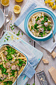 Penne pasta with sausage meatballs, peas, kale, creme fraiche and lemon sauce and parmesan cheese