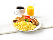 Scrambled eggs with sausages, tomatoes and toast, orange juice, coffee