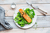 Salmon on a bed of green vegetables with mange tout