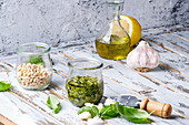 Basil pesto sauce in glass jar with fresh basil, olive oil, parmesan cheese, garlic, pine nuts, lemon on wooden kitchen table