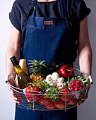 A person holding various groceries in a wire basket