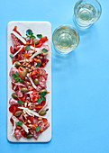 Salami and grilled peppers with almonds, capers and Grana Pandano