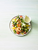 Spinach salad with fried prawns and avocado dressing