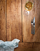 Cutlery and a glass of white wine on a wooden table