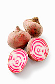 Chioggia beets, whole and halved against a white background